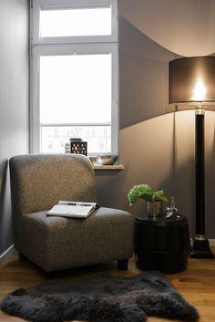 """Eine separate Sitzecke im Schlafzimmer schafft einen """"Raum in Raum"""" für einen ruhigen Rückzugsort. Mit dem Trio aus Sessel, Beistelltisch und Fellteppich verwandelt sich das sonst sehr verwinkelte Zimmer in ein wohnliches Ambiente. Accessoires in Silber ergänzen den schicken Einrichtungsstil."""