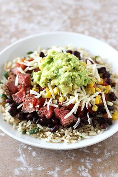 This Steak Burrito Bowl copycat recipe is loaded with beans, healthy cilantro lime brown rice, sweet corn salsa, and chunks of slightly spicy steak. YUM.