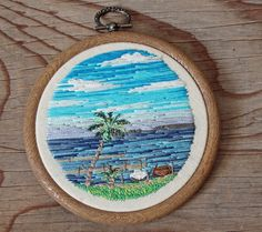 Sarah Buckley, aka IttyBittyBunnies, encapsulates beautiful natural landscapes into miniature embroidered pendants. Working in hoops that fit onto the tips