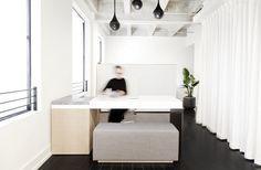 El mostrador de cita personalizada fue diseñado y construido con una sola hoja doblada de aluminio, lacado MDF, mármol y roble blanco.  La cortina blanca del suelo al techo esconde la cocina incorporada que era parte del altillo de Lee desde el principio.