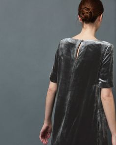 Simple shift dress in fluid, silk base/viscose pile velvet. Wide boat-ish neck. Elbow length sleeves. Keyhole opening, fastening with rouleau loop and self covered button. Pockets.