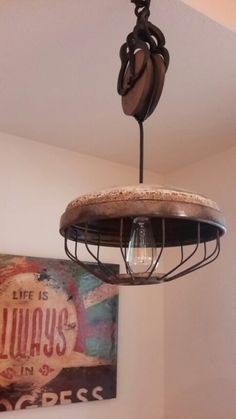 Farmhouse Style!  Old fan casing (a find in Round Top, TX) paired with a wooden pulley for the light over the kitchen table.