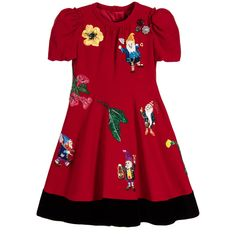 Girls short-sleeved red dress by Dolce & Gabbana. Made in lightly textured, viscose crepe with a silky smooth lining. It has a concealed zip fastener at the back with puffy sleeves and pretty ruching at the shoulders. The skirt is full and flared and trimmed in soft black velvet. This gorgeous 'Fairytale' themed dress has reference to Snow White and features delightful dwarf appliqués on the front, together with beautiful floral embroidery, sparkly jewels and shiny sequins.