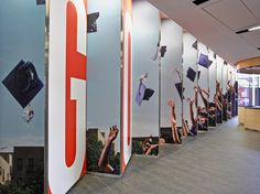 The founding Class of 2013 are immortalized on the reverse side of the sawtooth wall in a graduation cap toss photograph by Marc Ohrem-Leclef.