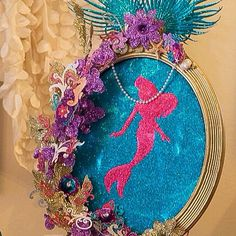 I love the way this Mermaid picture frame came out! It is such a fun, easy, & affordable project to try.  Tip: Use a picture frame you already have. 1) Cover the picture frame with blue glittered wrapping paper. 2) Draw, cut out, & glue Mermaid silhouette & place in the center. 3) Add sparkly purple, gold, & turquoise flowers/leaves to top & one side of the frame. 4)Add & layer sea life stickers & swirls to flowers & leaves. 5) Add & hot glue a acrylic pearl necklace for a touch of girly…