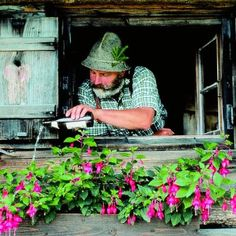 """Blumengiessen auf Bairisch.........  """"Watering Window Boxes the Bavarian Way""""........ And yes that IS a bottle of beer you see there. After all beer is considered as an official """"food"""" in Bavaria, even for fuchsia obviously......  Photo via Dein Bayern."""