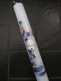 Elfenbeinfarbene Tauf-oder Kommunionskerze ,gestaltet mit einem Kreuz , das mosaikhaft in Regenbogenfarben zusammengesetzt ist. Unterhalb befinden sich Wellen und Fische in verschiedenen blauen...