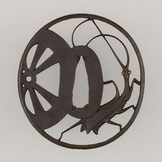 Tsuba, iron, gold, copper, depicting a praying mantis and a wheel.  19thC.