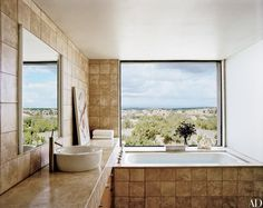 Clad in travertine tile, the master bath of former Vogue and Vanity Fair art director Charles Churchward's Sante Fe, New Mexico, home, built by architect Ralph Ridgeway, has a Boffi sink with fittings by Philippe Starck for Hansgrohe | archdigest.com