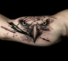 Piercing eyes on this eagle face bicep tattoo, with black paint splashes. This piece was created by Richard Blackstar.