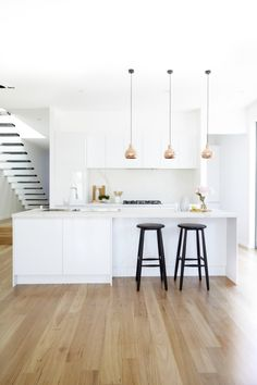 Kitchen: White cupboards, timber floors, copper pendants