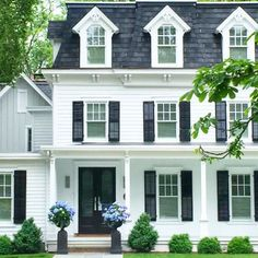 Cute simple cozy white house with black shutters, topiaries and sconces by the front door. Cute little brick walkway up to the porch. Home design decor inspiration ideas. Exterior Paint Colors, Exterior Design, Style At Home, Future House, Black Shutters, Window Shutters, Dream House Exterior, Colonial House Exteriors, White Houses