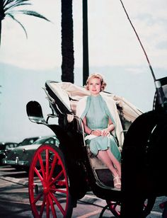 Grace Kelly wearing a blue dress with a white cardigan draped over her shoulders as she rides in a horse drawn carriage, 1955.