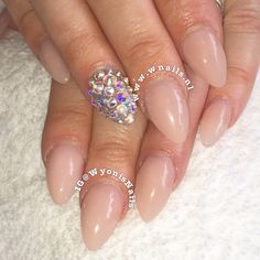 Nude almond/oval acrylic nails with a Swarovski crystal accent nail. Done with cover pink. Great and simple look for brides & weddings