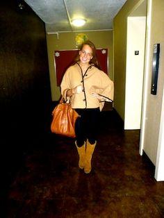Elizabeth in a camel colored poncho coat.