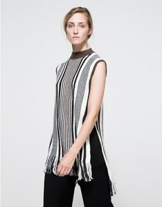From Farrow, an ultra soft tank sweater with a long silhouette in white and tonal brown vertical stripe pattern.  Features tall collar, ribbed neckline, ribbed cuffs, tall side slits with finished edge, fringe hem, straight cut with straight fit.  •Sof