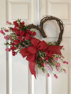 CURRENTLY SHIPPING IN 3 DAYS Or LESS! ADORABLE VALENTINE HEART SHAPED WREATH. Grapevine wreath accented with Greenery, Red Flowers,Pink Wildflowers and a Red Burlap bow . Wreath is approximately 15 wide and 17 long. Available in Purple and Yellow too! Wreaths are made when ordered and