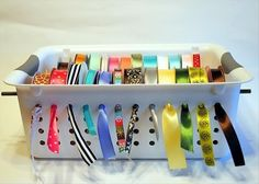 A plastic basket, a couple of dowels and you have a very functional ribbon organizer & dispenser!