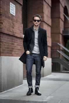Dress in Grey Polo, Black Overcoat, Charcoal Zip Sweater, a pair of Navy Jeans and Black Boots