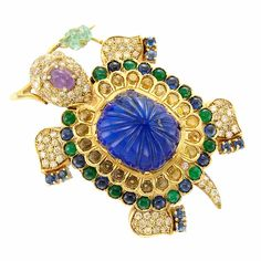 Gold, Carved Lapis, Yellow Diamond and Gem-Set Turtle Clip-Brooch, Demner  18 kt., one cushion-shaped fluted lapis ap. 19.0 x 16.2 x 13.6 mm., 91 round yellow diamonds ap. 2.70 cts., 20 round yellow sapphires, round cabochon sapphires  emeralds, one cabochon pink sapphire, one carved emerald, signed Demner, NY-VIE (Vienna), ap. 22 dwts. gross.