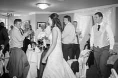 Bride and groom arriving into wedding function room with their guests clapping.