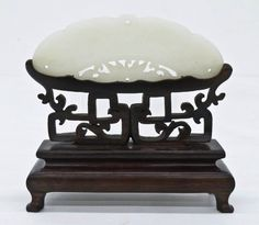 Lot 139- A Chinese White Jade Pendant on Stand 4.5''x4.75''. A fine jadeite pendant of butterfly or moth shape. Pierced carved with blossoming lotus flower and opposing birds with peaches in center. Pale celadon to white in color. Comes on original fitted carved rosewood stand, missing one leg. Excellent condition. 19th century, Qing dynasty.