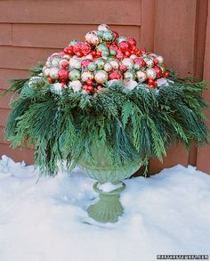 pile of ornaments and a double wreath sit atop a decorative urn. how to