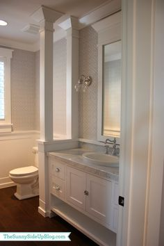 division detail between toilet and vanity, half wall with columns and wainscot trim continuing around over backsplash