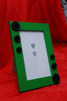 Cornice verde con bottoni neri