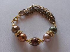 Bracciale con perle sfaccettate, montato con componenti in metallo coloro oro e catene di vari colori. Realizzazione artigianale.
