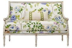 Colorful floral upholstery modernizes this traditional settee,.