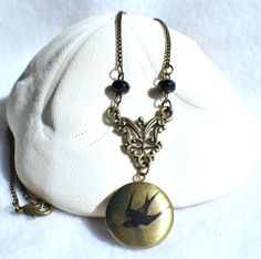 Round locket with bird on front cover adorned with black beads and bronze accents