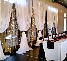 Moments In Time Wedding & Event Rentals. Head table reception backdrop ~ black mirror organza, white sheers, fairy lights and crystal curtains.