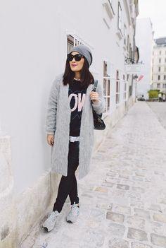 Winter outfit: grey knit hat, white shirt, black sweater, grey coat, black skinny jeans, grey sneakers, black bag