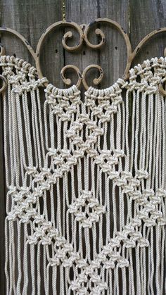 Large macrame made on distressed tan ornamental iron with 1/8th inch off white cotton rope. 30 inches wide by 42 inches long