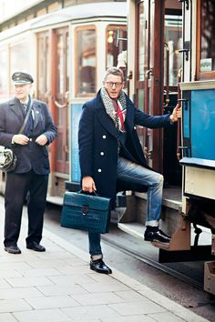 Swedish. Scandinavian. Fashion. Men. Clothing. Proper. Dressed. Minimal. Clean. Fresh. Blue Jeans. Worn. Leather. Great Coat. Winter. Scarf. Tram. Color. Glasses & Briefcase. Red & Blue. Pattern. Style. Outfit. Slim.