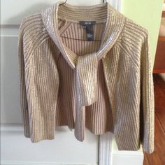 Long sleeve gold cardigan Beautiful gold shimmery wool cardigan by Per Se. 100% wool. This top can be tied in the front or left open. It's in excellent condition. I don't believe it has ever been worn! Don't miss out on this deal. It's much more beautiful in person!! Thanks for looking. Per Se Sweaters Cardigans