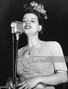 American singer Kay Starr, wearing an orchid in her hair and a heart-shaped locket, singing behind a microphone.