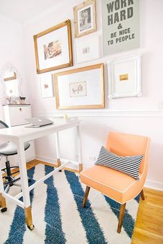 white desk, colorful and comfy chair, and white walls with an art grouping