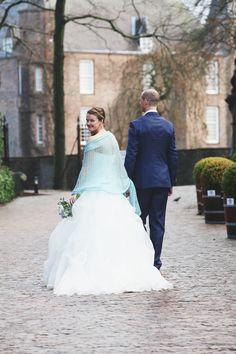 bruidspaar loopt hand in hand met slot zuilen op de achtergrond