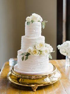 White roses topped three tier wedding cake: http://www.stylemepretty.com/2016/08/19/rustic-foxhall-resort-wedding/ Photography: Amy Arrington - http://www.amyarrington.com/