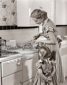 1950s HOUSEWIFE IN KITCHEN DECORATING CAKE ON STOVE WITH PASTRY GUN WHILE LITTLE DAUGHTER WATCHES