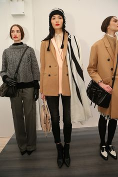 Camel coat over layers of pink and beige, black leggings, boots, and an off white varied width striped scarf.