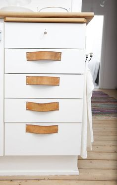 Leather straps as handles on a kitchen cabinet