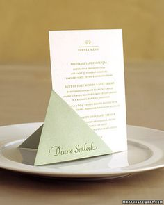 Use an easy origami fold to create a stand for the menu card. To make one for a 4-by-6-inch menu card, you'll need an 8 1/2-inch square of decorative heavyweight paper.Menu Stand How-To1. Fold the square in half diagonally, wrong sides facing, to make a triangle, and lay it with fold up.2. Use a pencil to make a small mark 5 inches from left corner. Using that mark as your guide, fold left point to right edge, as shown.3. Flip shape over; repeat step 2.4. Fold the bottom point up.5. ...