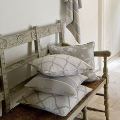 Clarke and Clarke -  Ribble Valley Fabric Collection - Grey wood bench with carved backrest, woven straw effect seat, and four grey, blue and cream cushions