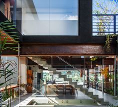 When entering the home, the interior unfolds via a series of verdant walkways which lead out toward the property's large living spaces and infinity pool