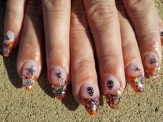 first an only attempt at stiletto nails. orange gel with glitter peices an mylar inlaid. with black stamped art