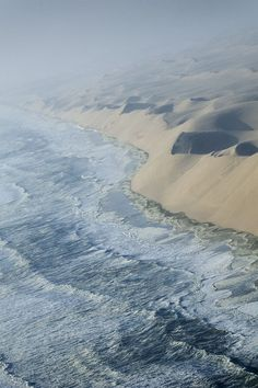 Ocean waves colliding with the sand dunes at the edge of the Namib Desert.
