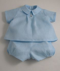 Ice blue linen baby suit. Two piece romper suit in ice blue fine handkerchief linen. A-line angel top with decorative front button tab and pleats. Back buttons. The romper bottoms have side openings, adjustable elastic in the back waist and button tabs. Underleg buttons and fully lined in cotton lawn. Shown here with our white …